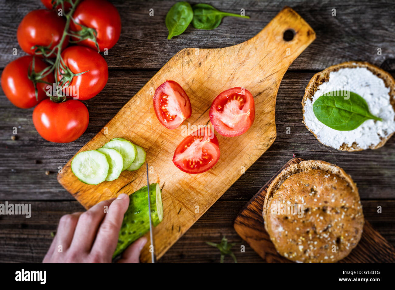 Chef cutting vegetables for salad. Process of cutting vegetables to make a healthy sandwich. Top view, selective - Stock Image