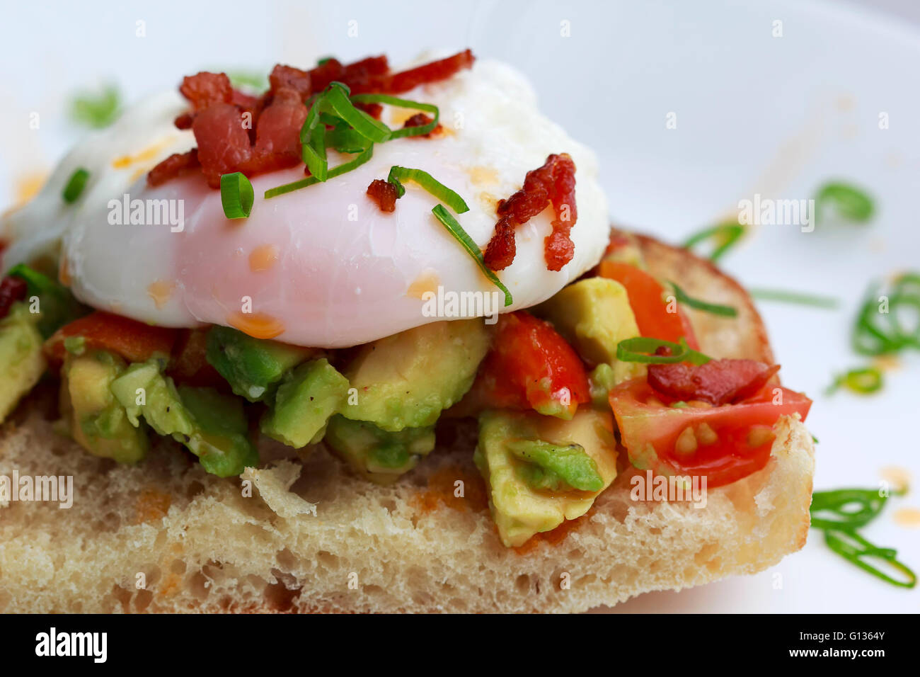 Poached eggs bacon tomatoes and avocado on toast Stock Photo