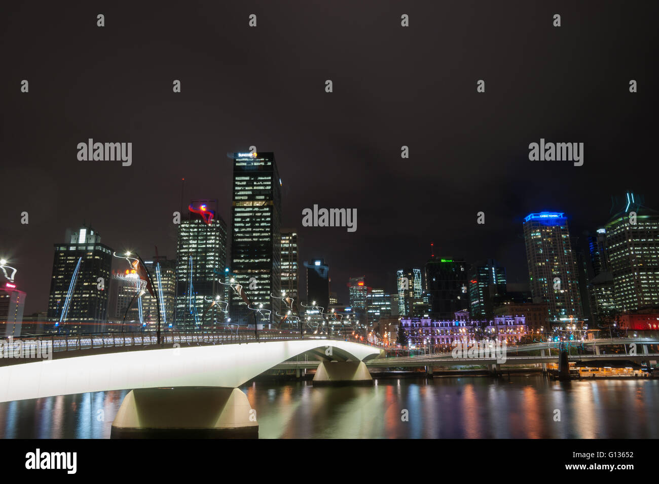 Brisbane Victoria Bridge iluminated against dark and city building lights and colr reflections in calm water of - Stock Image