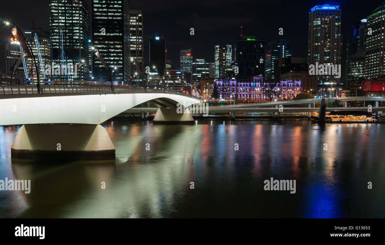 Brisbane Victoria Bridge illuminated against dark and city building lights and color reflections in calm water of - Stock Image