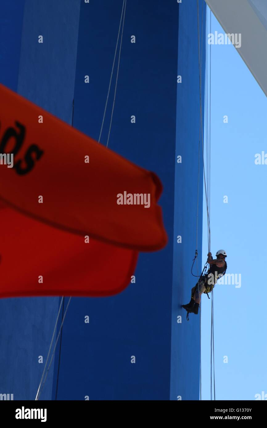 Person wearing a hard hat abseiling down a bright blue painted tower with a red sail in the foreground Stock Photo