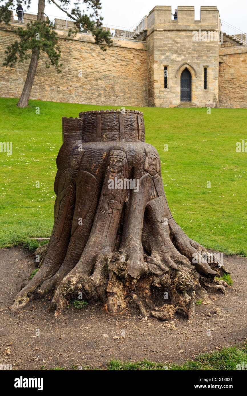 Tree stump carved with figures related to castle. Carved by Helena Stylianides. - Stock Image