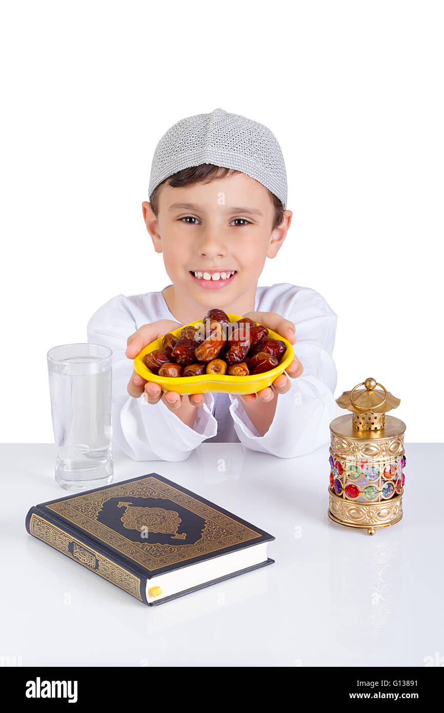 Little Muslim kid smiling while presenting a dish of dates for iftar - showing generosity  of Ramadan - Stock Image