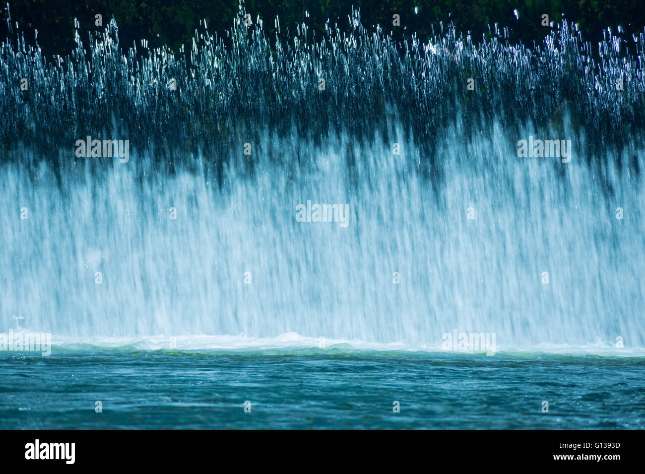 CURTAIN OF FRESH WATER CASCADES OVER SPILLWAY INTO CALM POOL ON SMALL RIVER - Stock Image