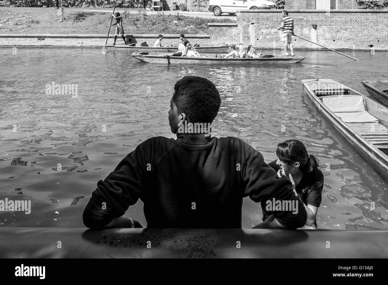 A boy man guide waits along the shore of the cam river in cambridge cambridgeshire in may on a hot sunny sun day Stock Photo