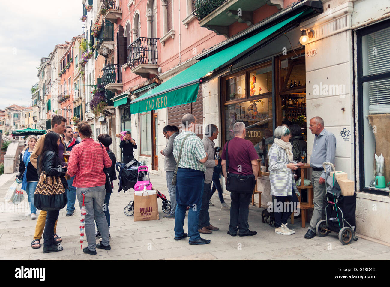 Crowd of people drinking outside bar in Venice - Stock Image