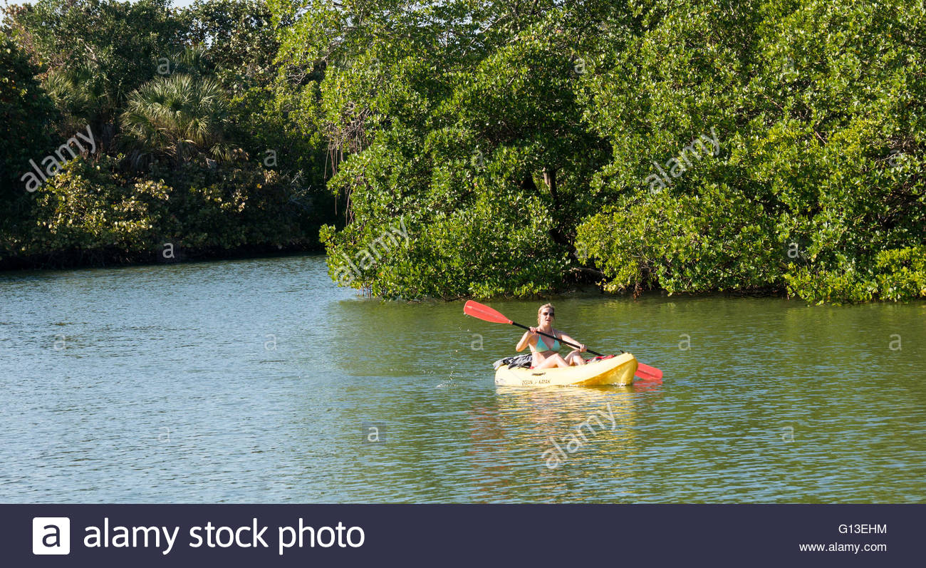 A woman kayaks along a waterway at Lovers Key State Park in Florida Stock Photo