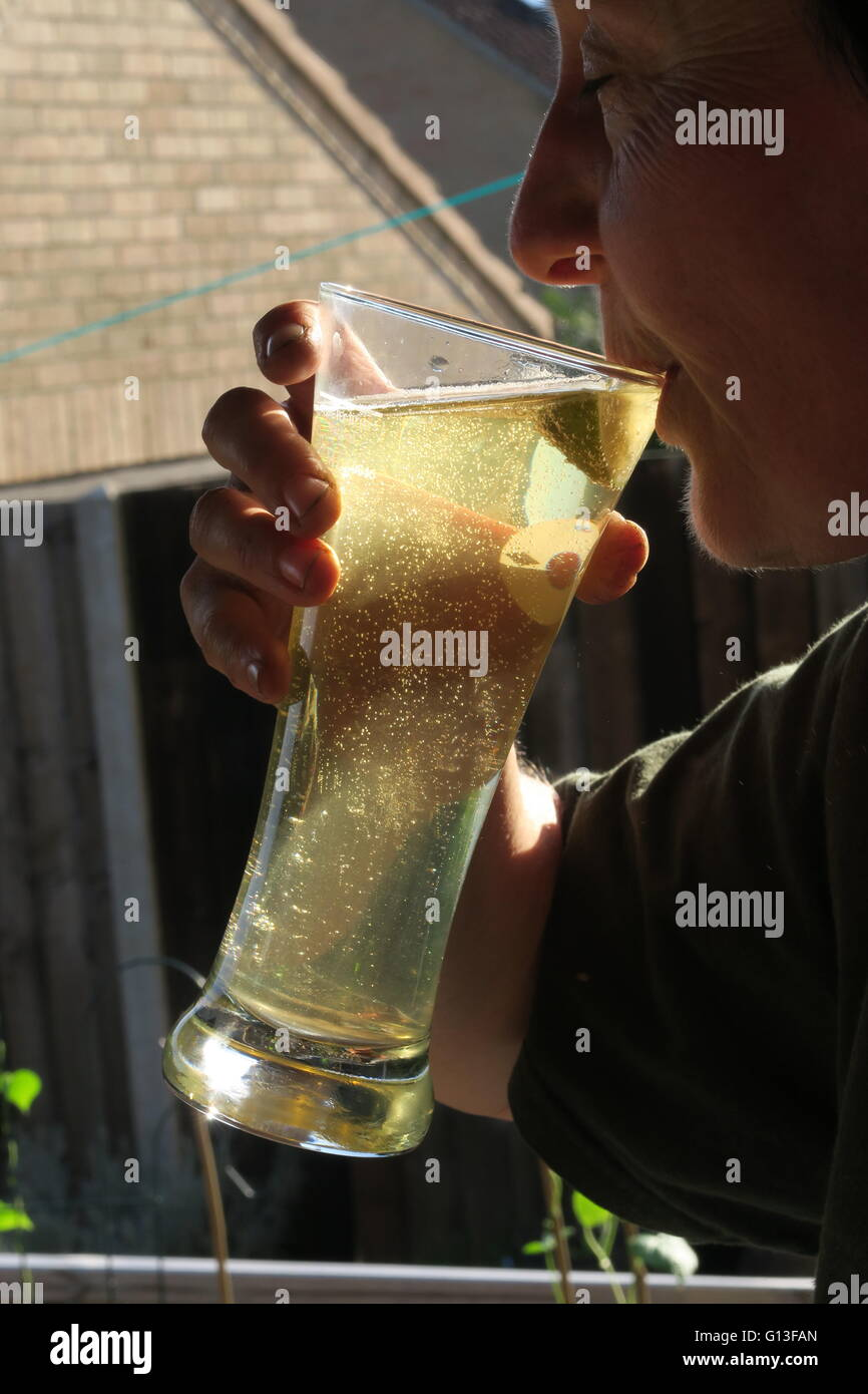 Enjoying Homebrew cider after a hot day in the orchard - Stock Image