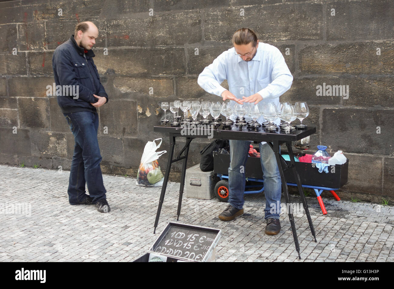 Glass harp - street entertainer playing music using wine glasses - Stock Image