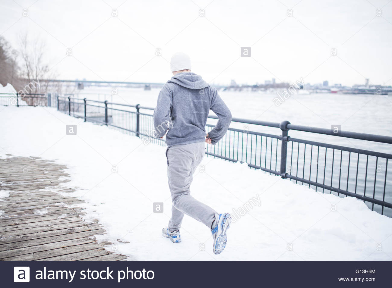 Young man in jogging pants working out along water, Montreal, Quebec, Canada - Stock Image