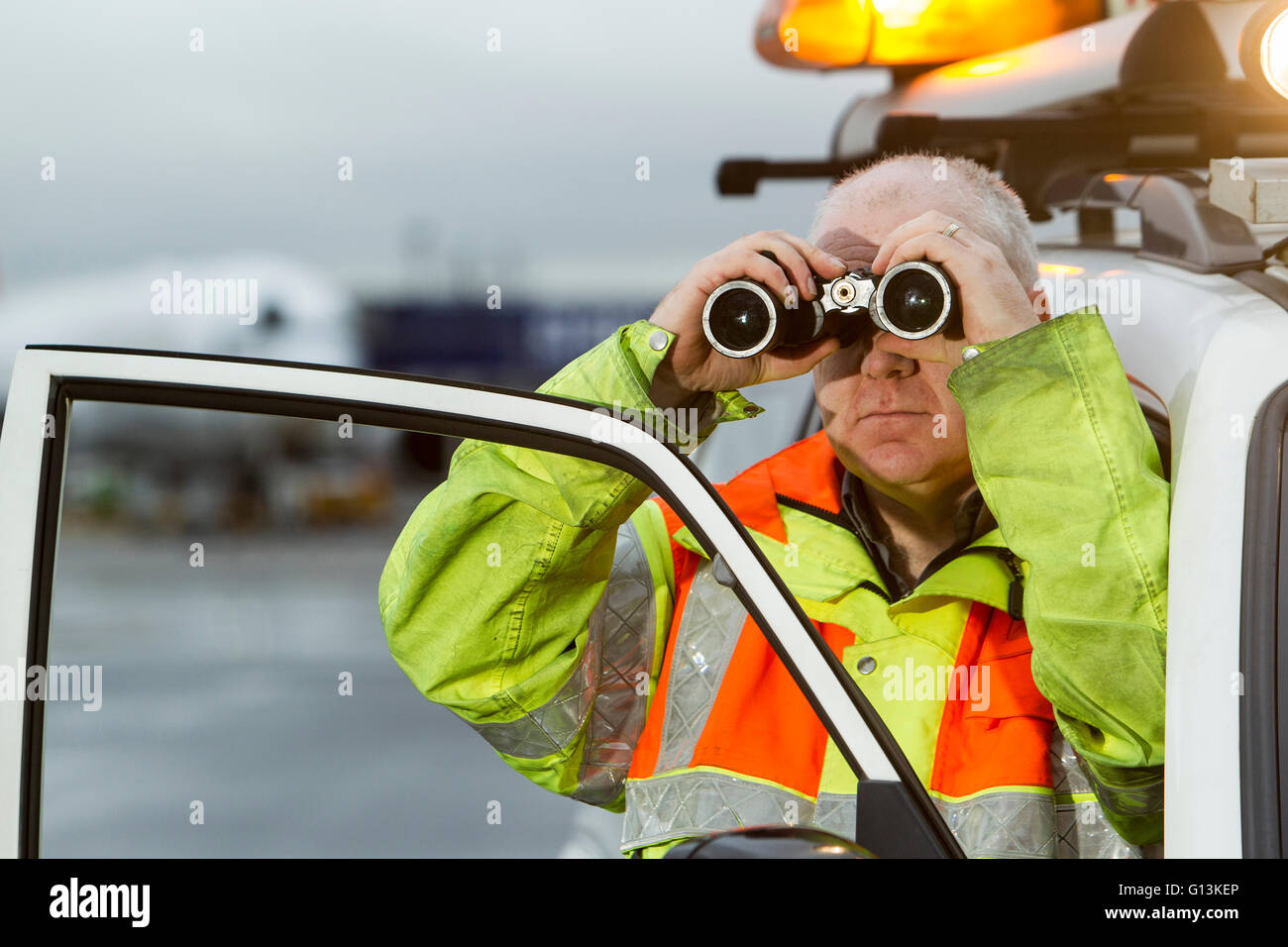 Ground Crew on runway at Glasgow Airport with landing lights in background Stock Photo