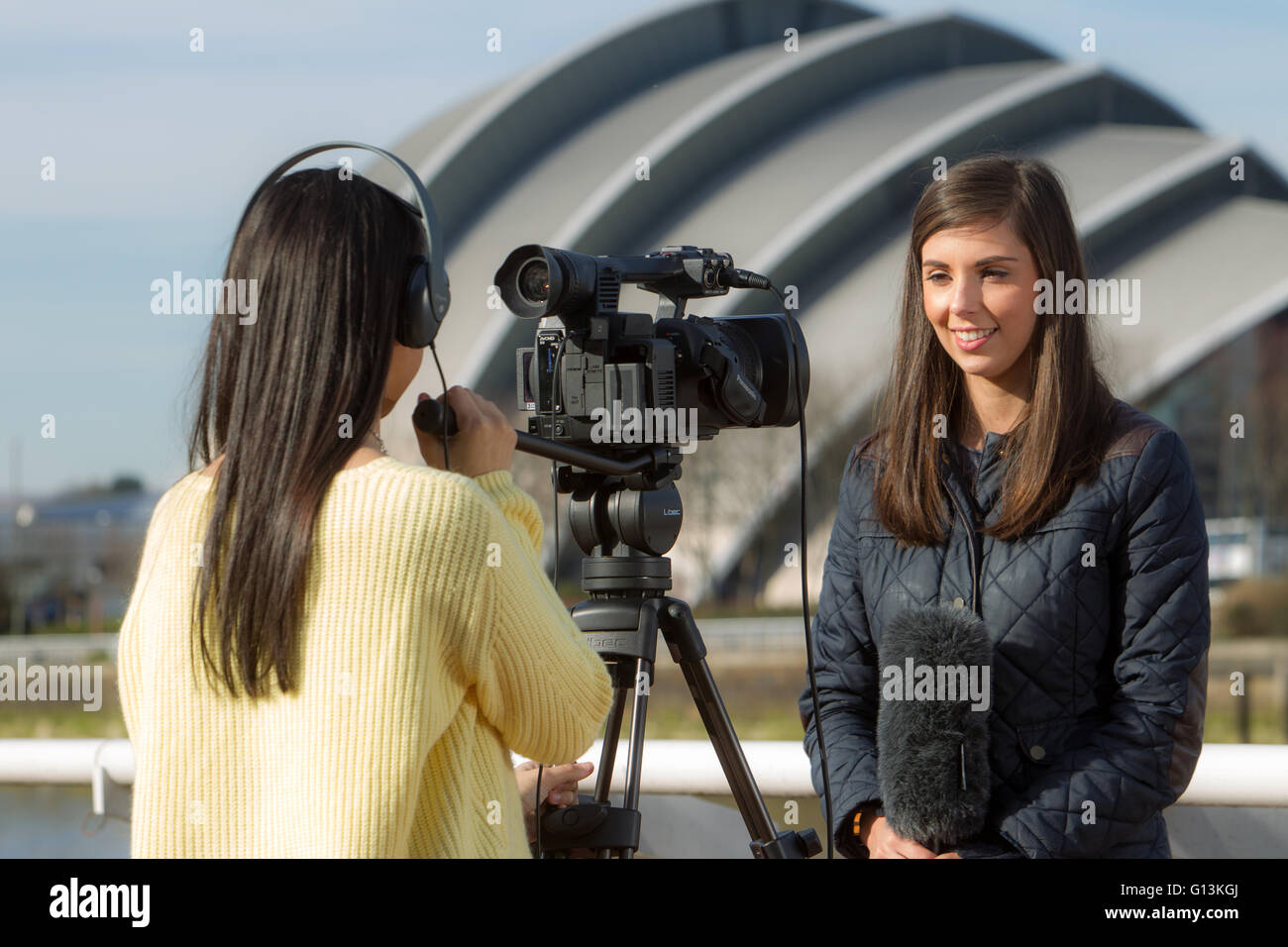 Media students filming in Glasgow by the river clyde - Stock Image
