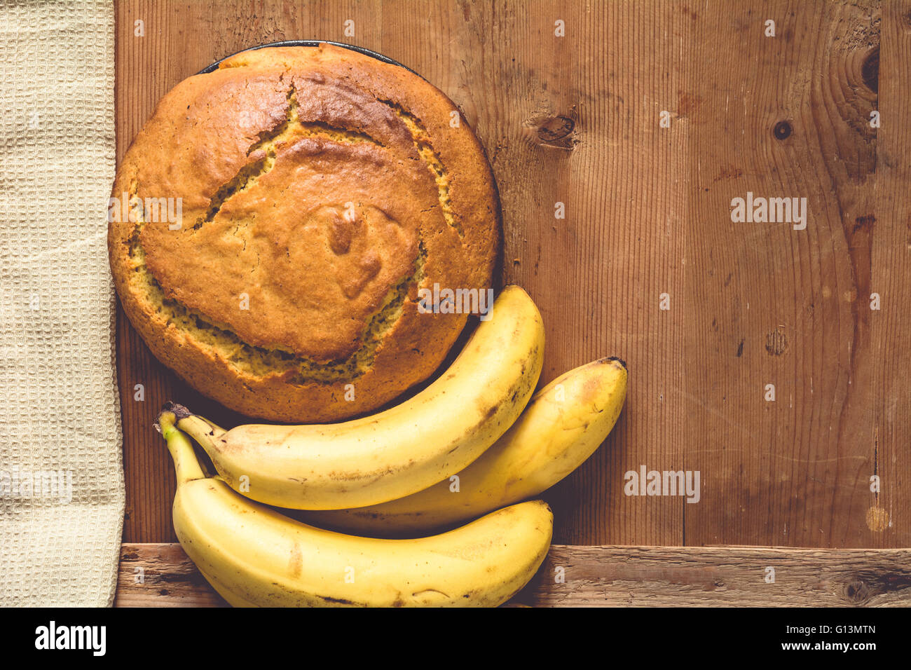 Homemade banana bread with chocolate and peanuts on wooden background, top view - Stock Image
