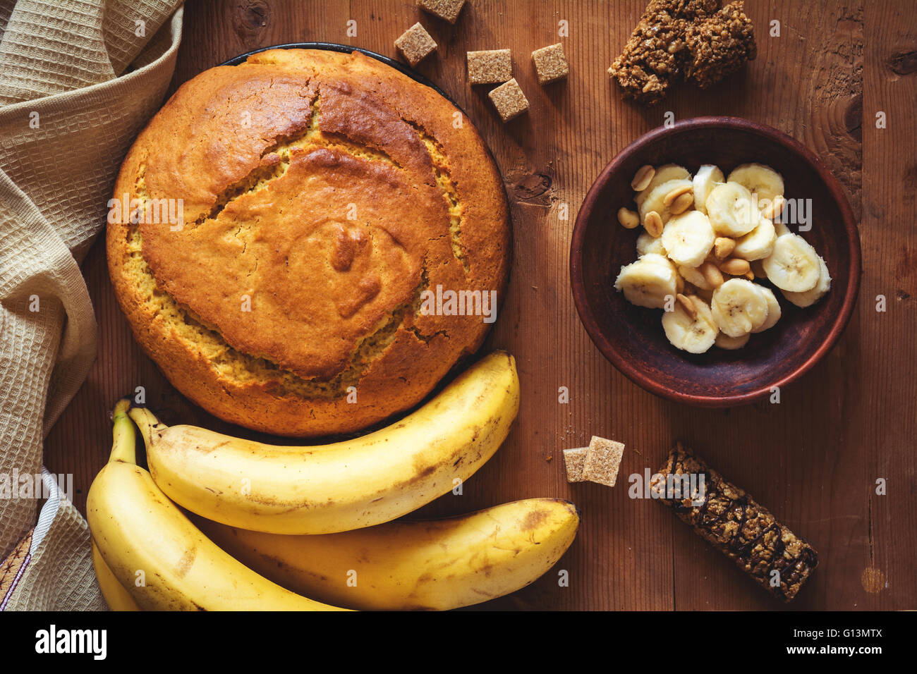 Round loaf of freshly baked banana bread with peanuts, dark chocolate and brown sugar on wooden backdrop. Table Stock Photo