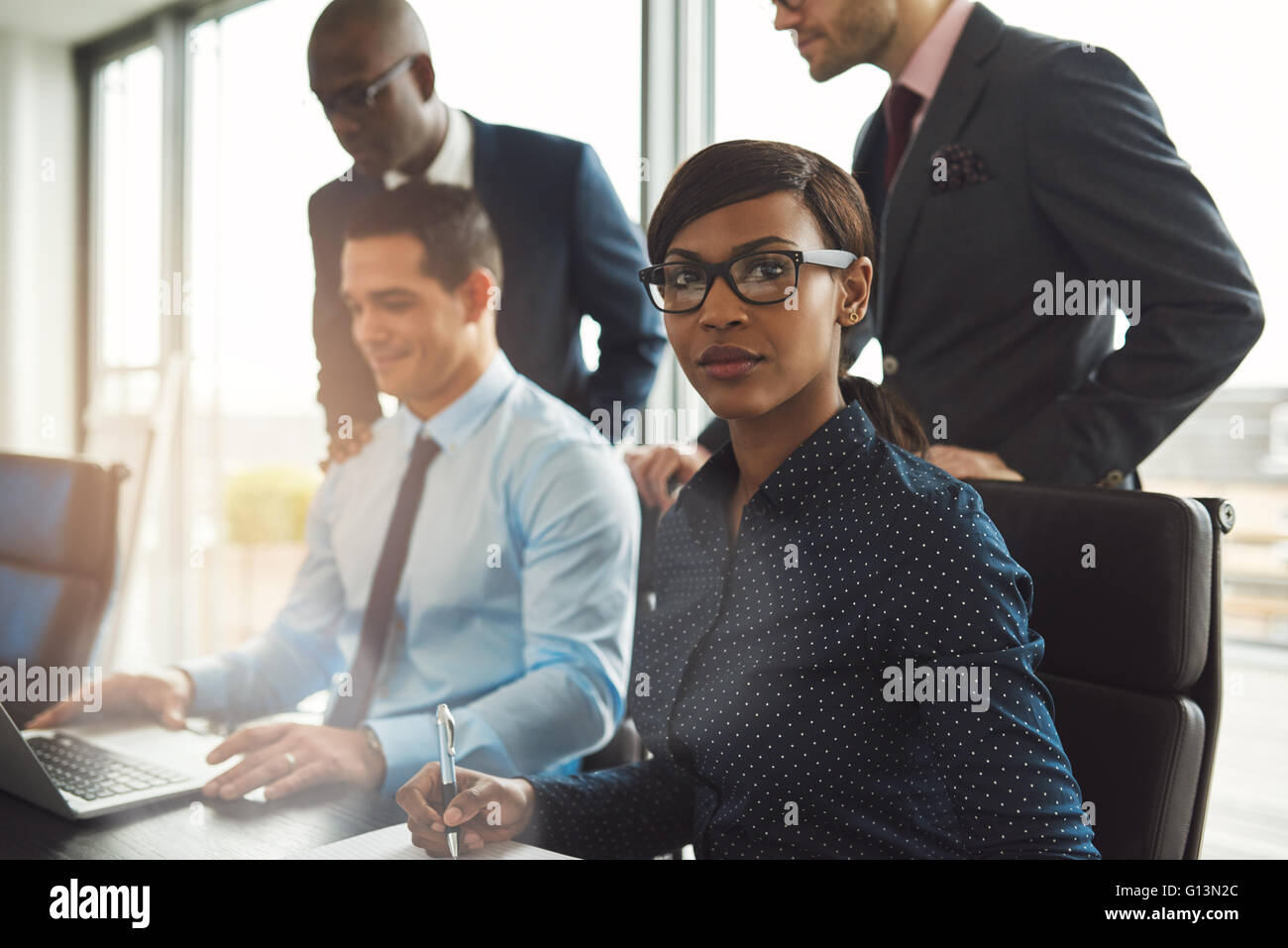 Attractive serious businesswoman wearing eyeglasses and blue blouse sitting at conference table with three male - Stock Image