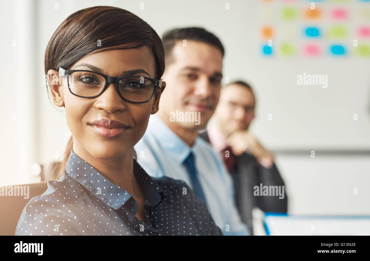 Beautiful smiling business woman wearing eyeglasses and white polka dotted shirt seated with male co-workers at - Stock Image
