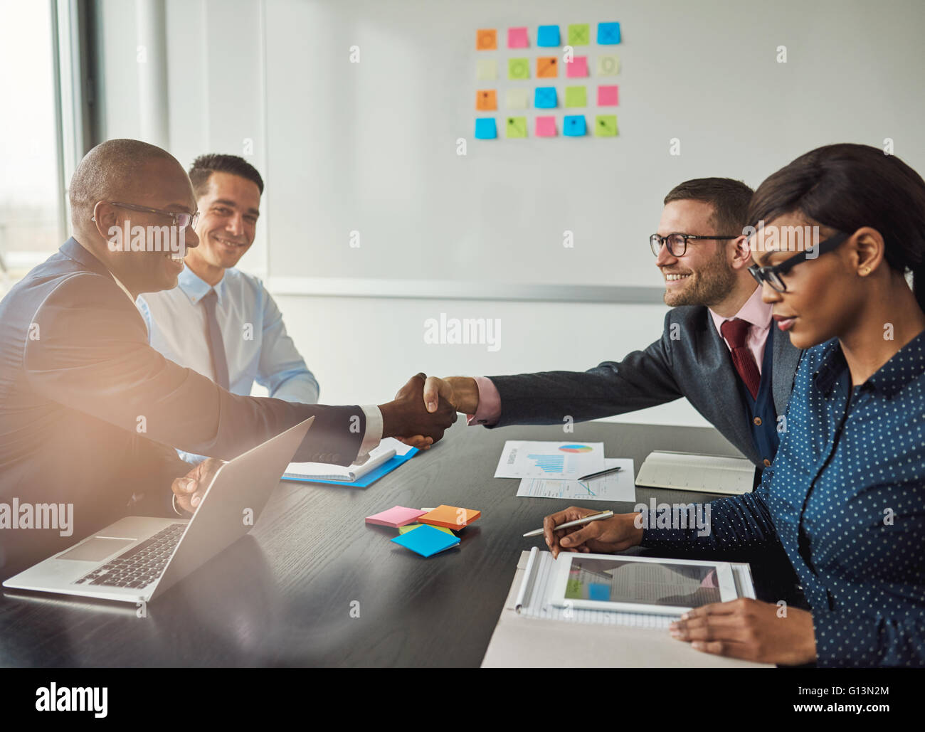 Multiracial team concluding a business agreement reaching across the table to shake hands with pleased smiles with - Stock Image