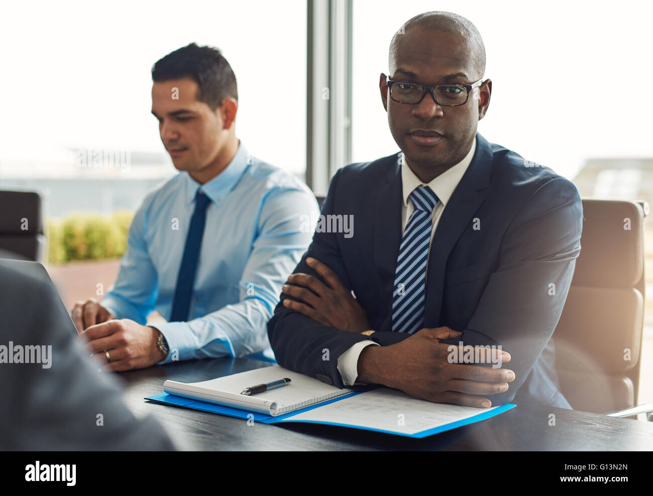 Executive multiracial business team having a meeting in the office with focus to a serious middle-aged African American - Stock Image