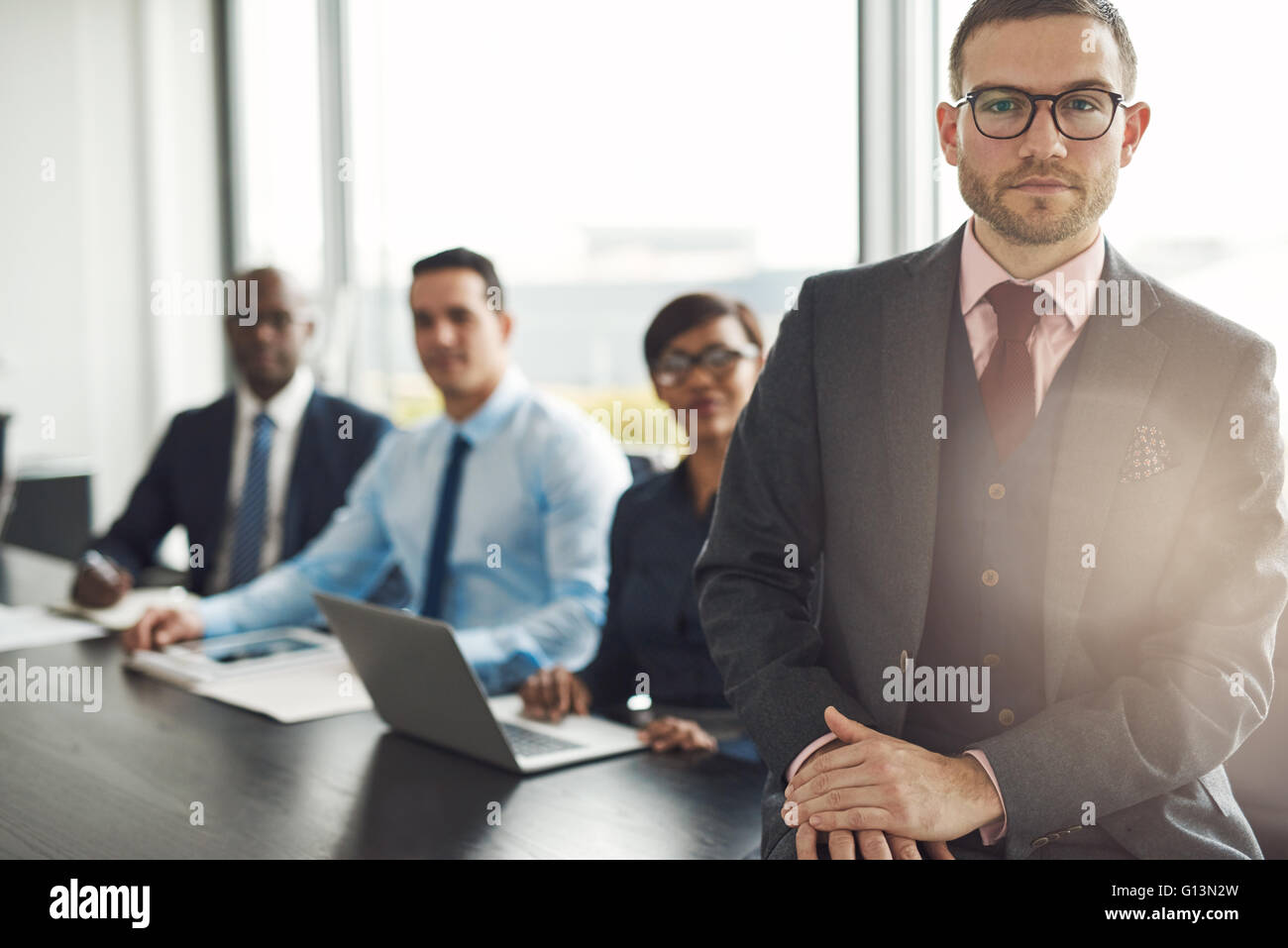 Handsome Caucasian executive with three employees sitting on edge table with back to large bright office window - Stock Image