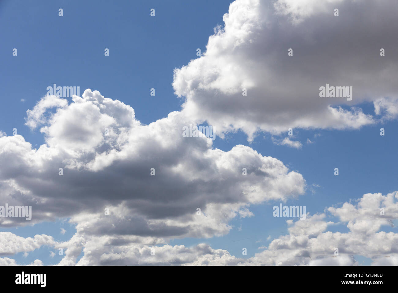 White fluffy clouds against a bright blue sky - Stock Image