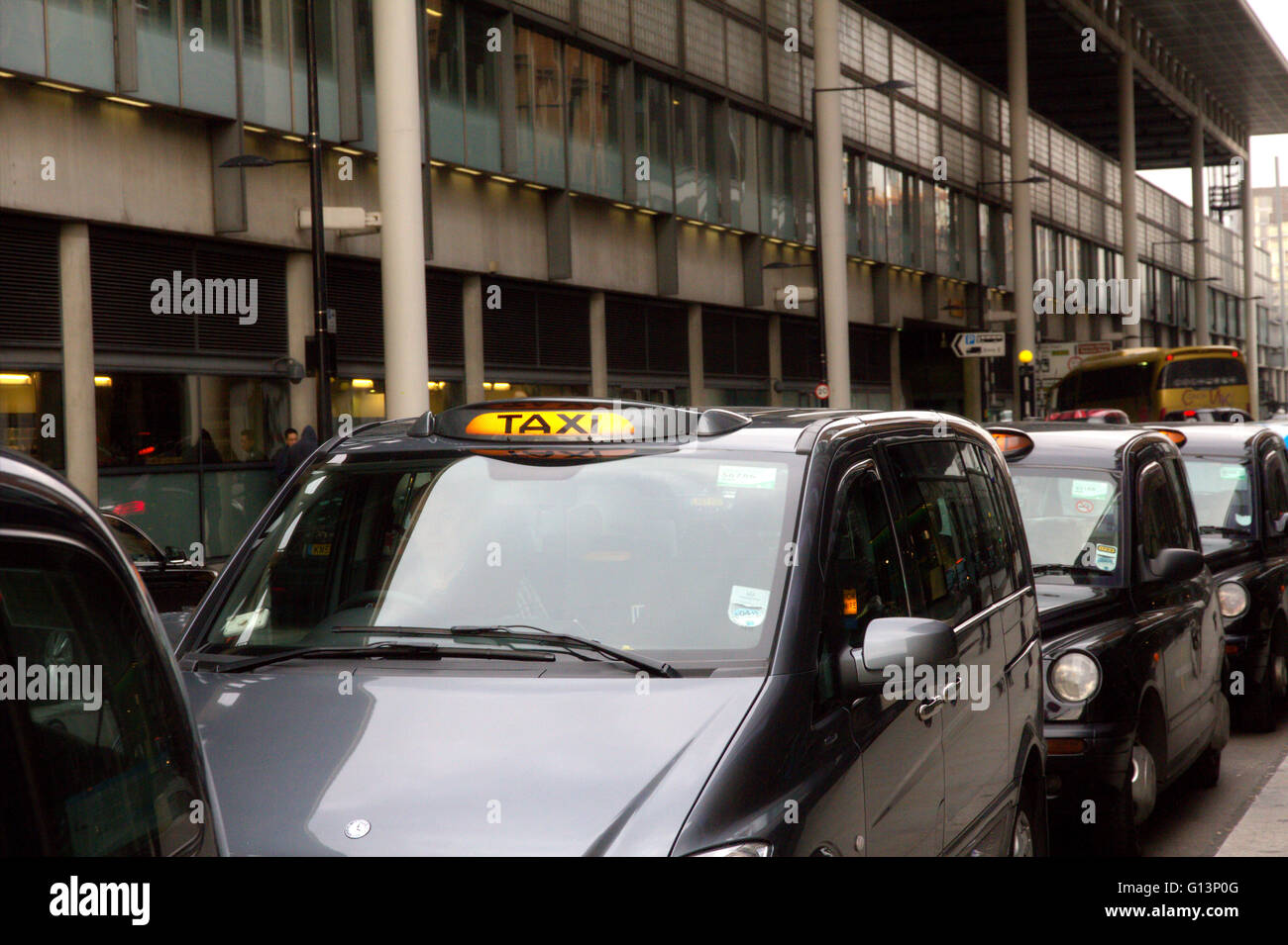 A queue of London black cab taxis in a row at a taxi rank, waiting to pick up passengers near Kings Cross station Stock Photo