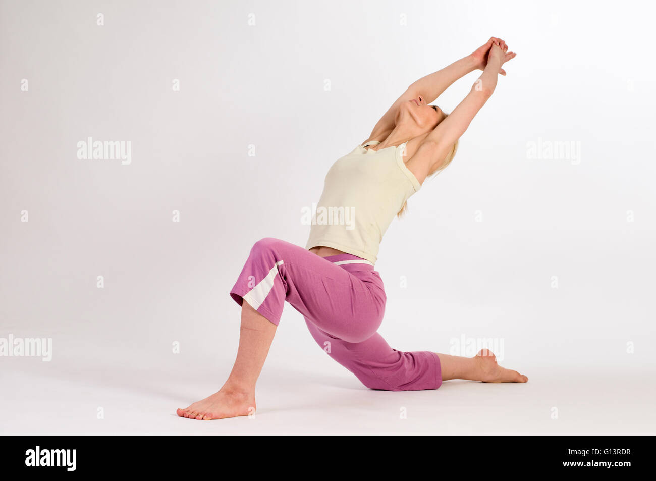 young woman on a white background in yoga position Crescent side from the front - Stock Image