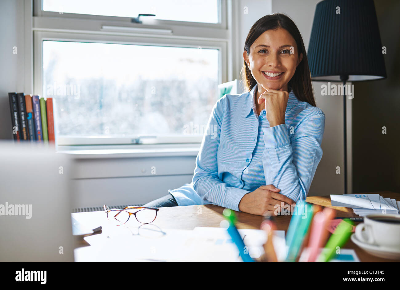 Cheerful woman with hand on chin wearing blue shirt while seated at desk covered with papers, coffee and eyeglasses - Stock Image