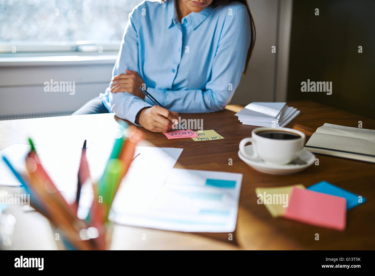Female small business owner working from home sitting at her desk making notes on sticky memo cards , close up view - Stock Image