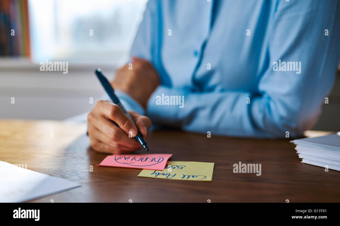 Creative young woman drawing designs in the office on colorful memo pads as she sits at her desk , close up view - Stock Image