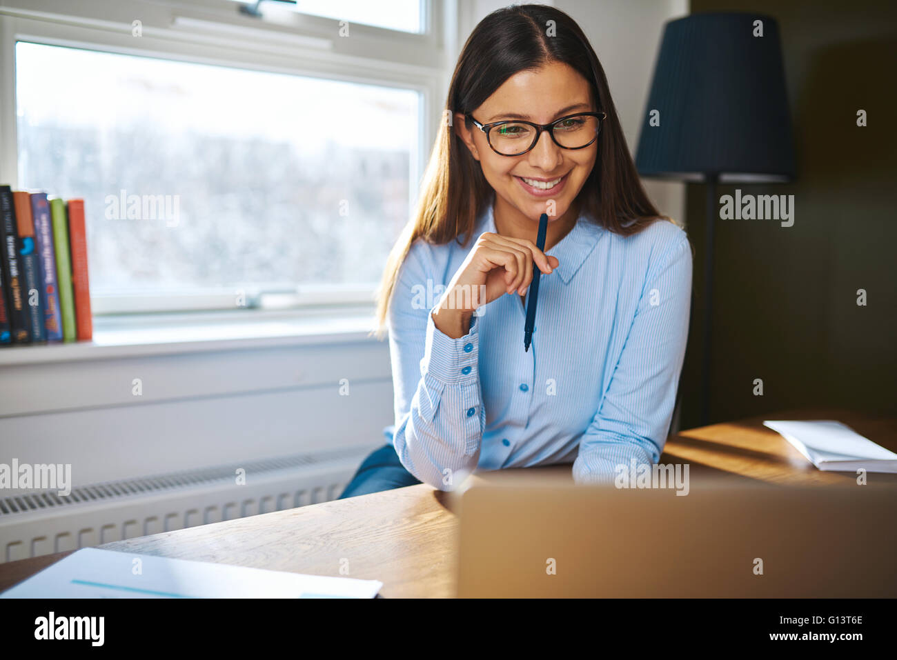 Smiling young businesswoman working at home sitting at her desk reading information on the laptop with a pleased - Stock Image