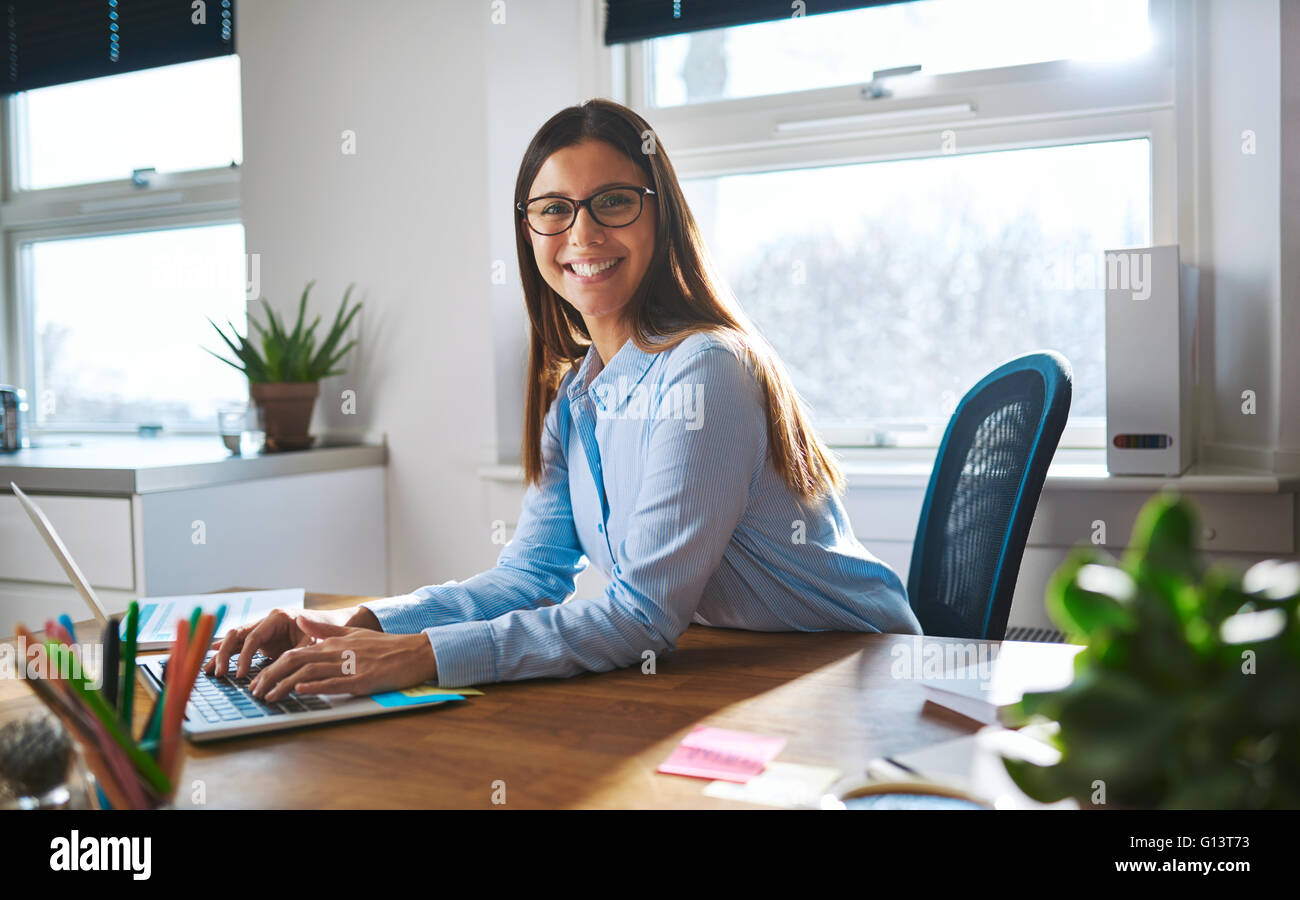 Enthusiastic woman with smile and eyeglasses working at bright sunny desk with windows in background - Stock Image