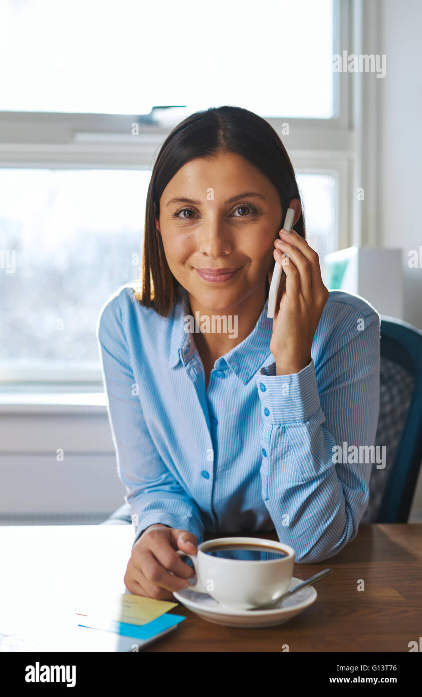 Young business entrepreneur on a mobile phone call sitting at her desk smiling as she listens to the conversation - Stock Image
