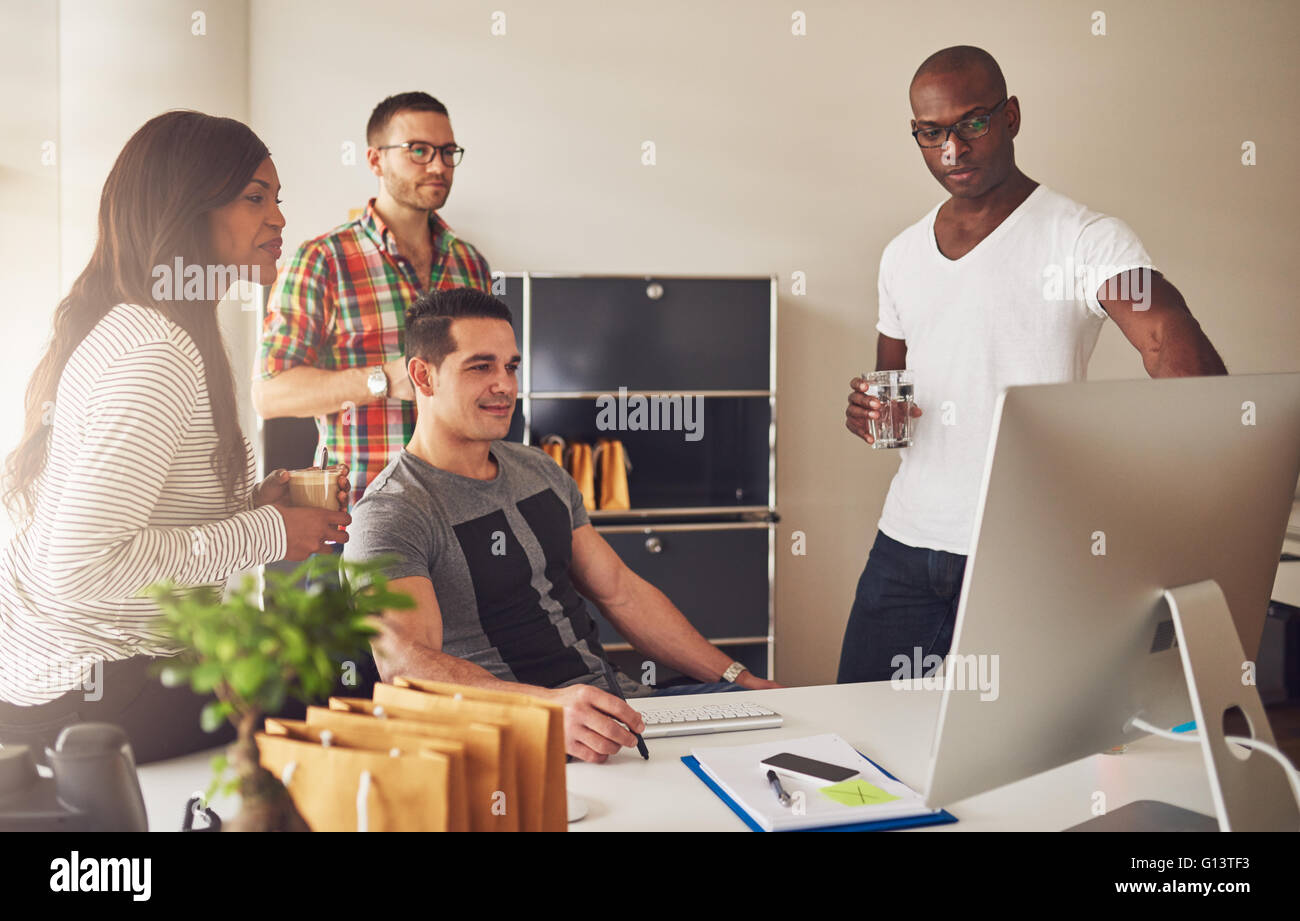 Diverse group of multi-ethnic young adult business people assembled around desk looking at something on their computer - Stock Image
