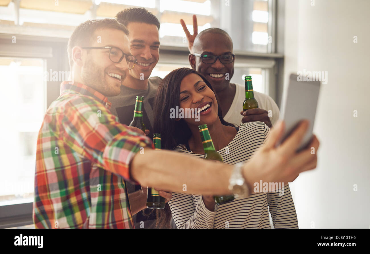 Friends at work taking self portrait with camera phone while holding green glass bottles of beer in office party Stock Photo
