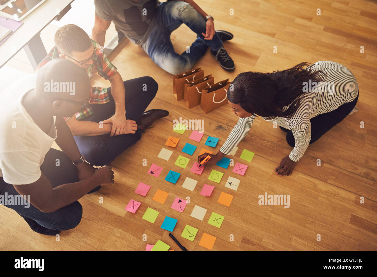 High angle view on female business owner writing on various sticky notes for workers on floor in small office with Stock Photo