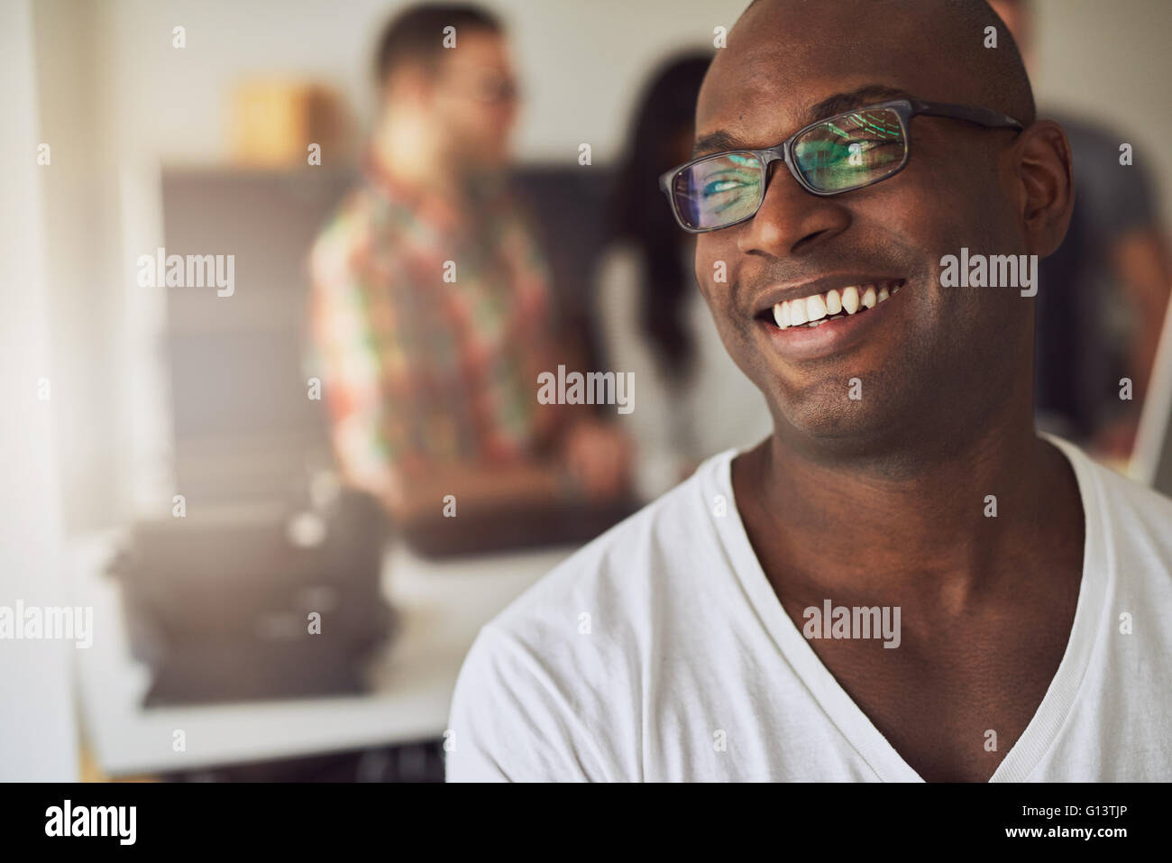Close up of handsome smiling worker in white shirt and eyeglasses with three out of focus employees behind him in - Stock Image
