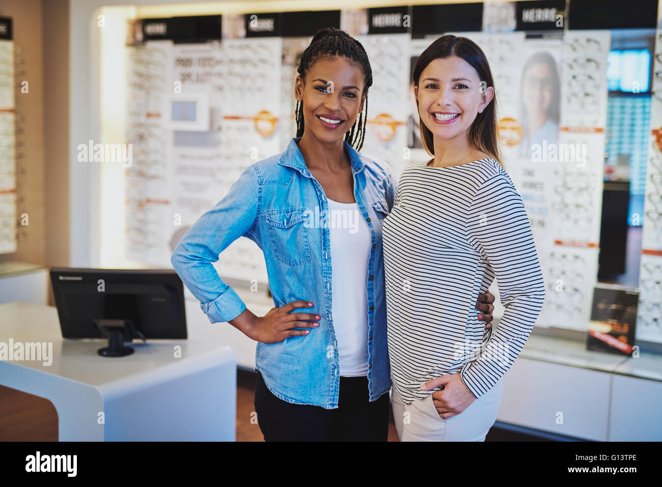Multiracial entrepreneurs in their shop looking welcoming at camera - Stock Image