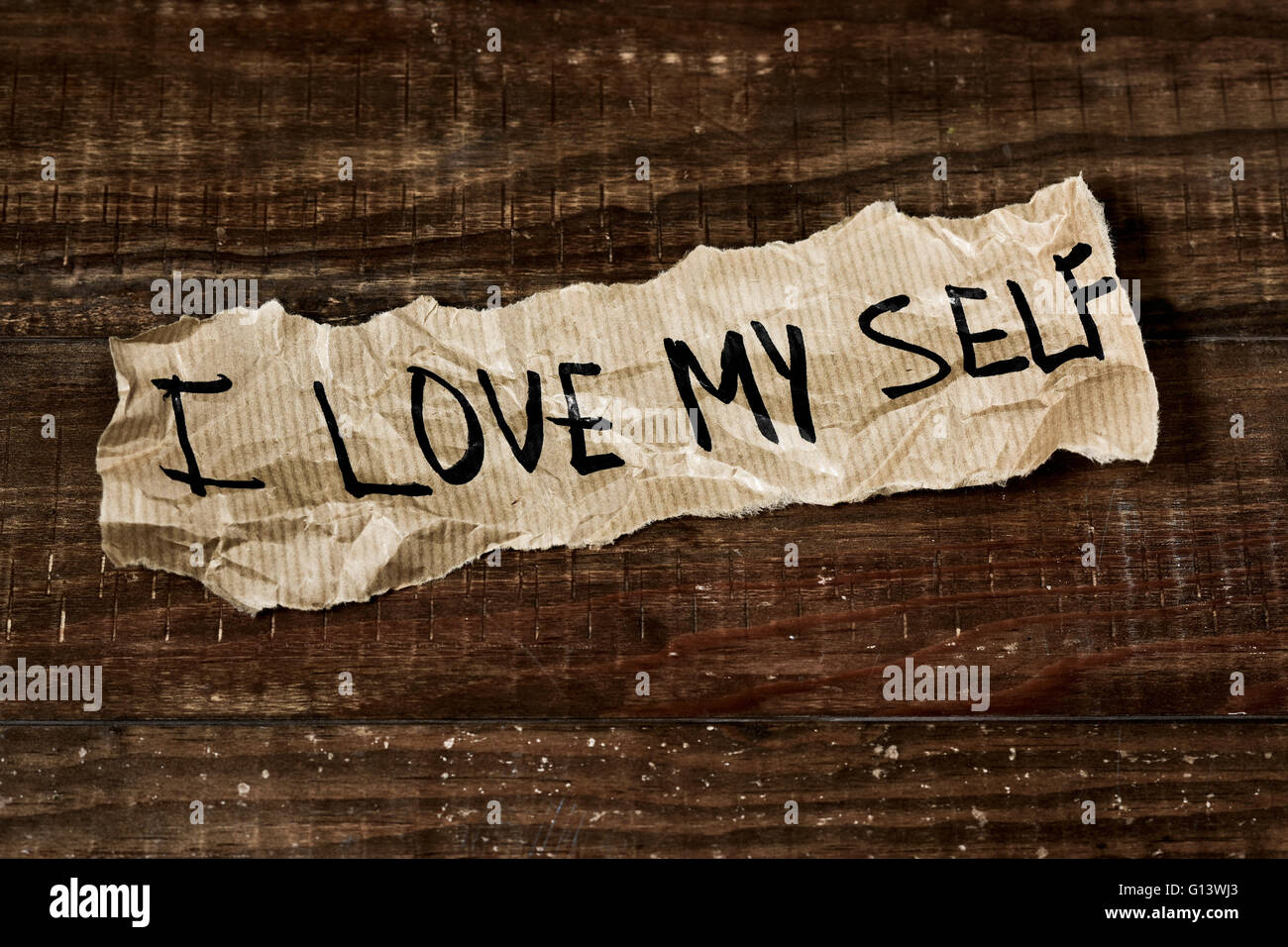 the text I love myself written in a piece of paper, placed on a rustic wooden surface - Stock Image