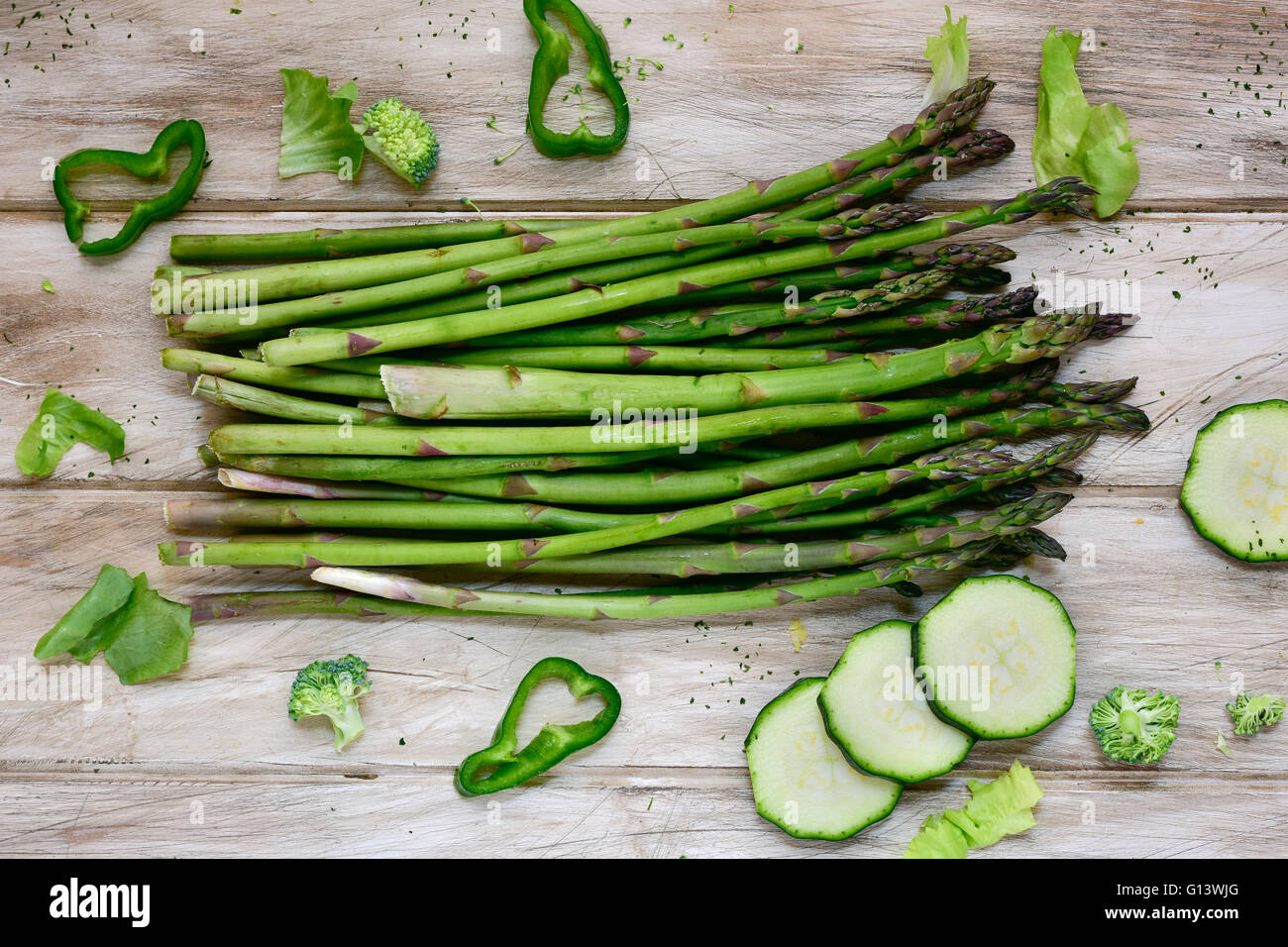 high-angle shot of some different raw green vegetables, such as green pepper, asparagus, broccoli or zucchini, on - Stock Image