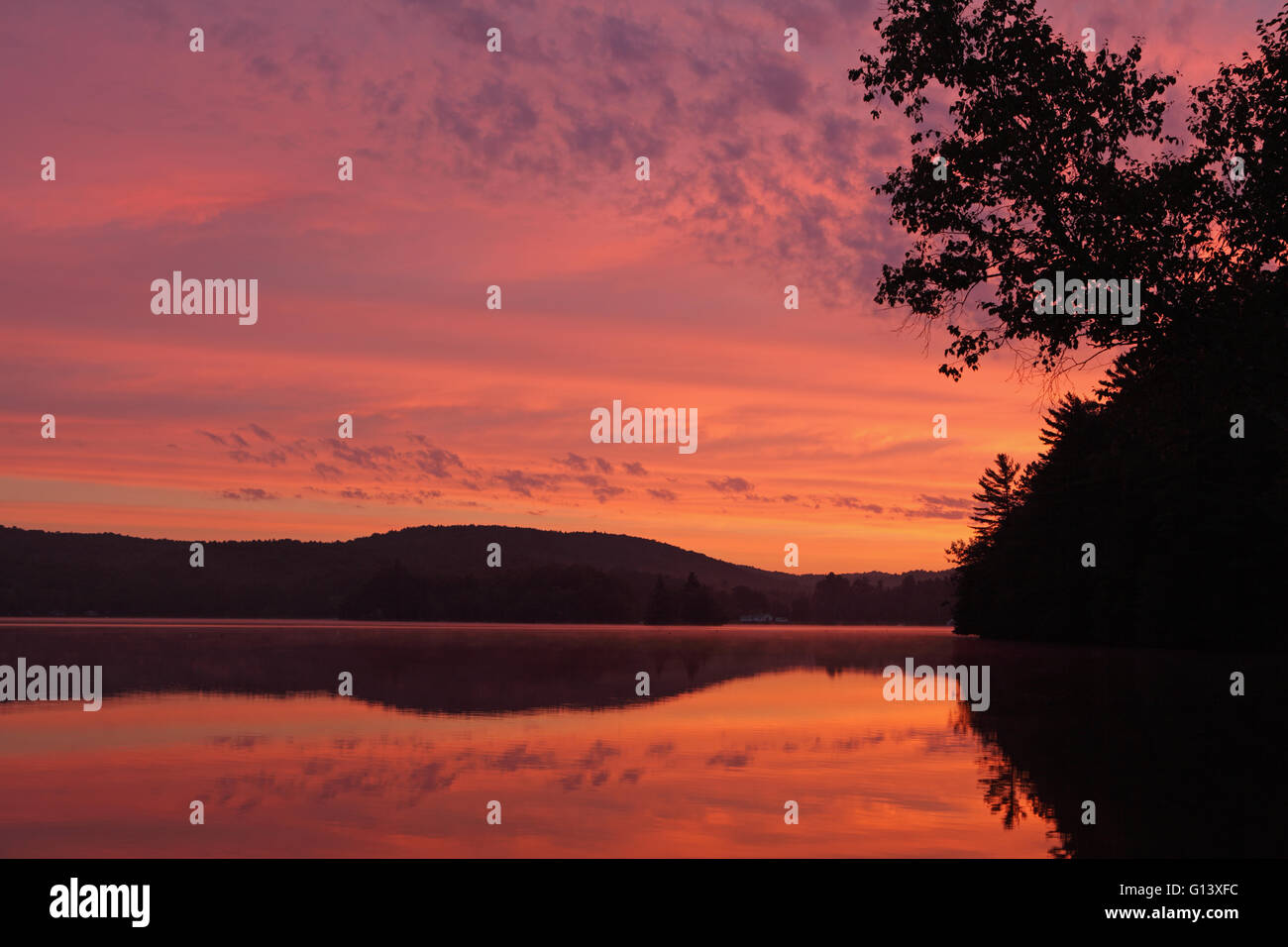 Landscape sunrise over a lake in Western Vermont with red clouds Stock Photo