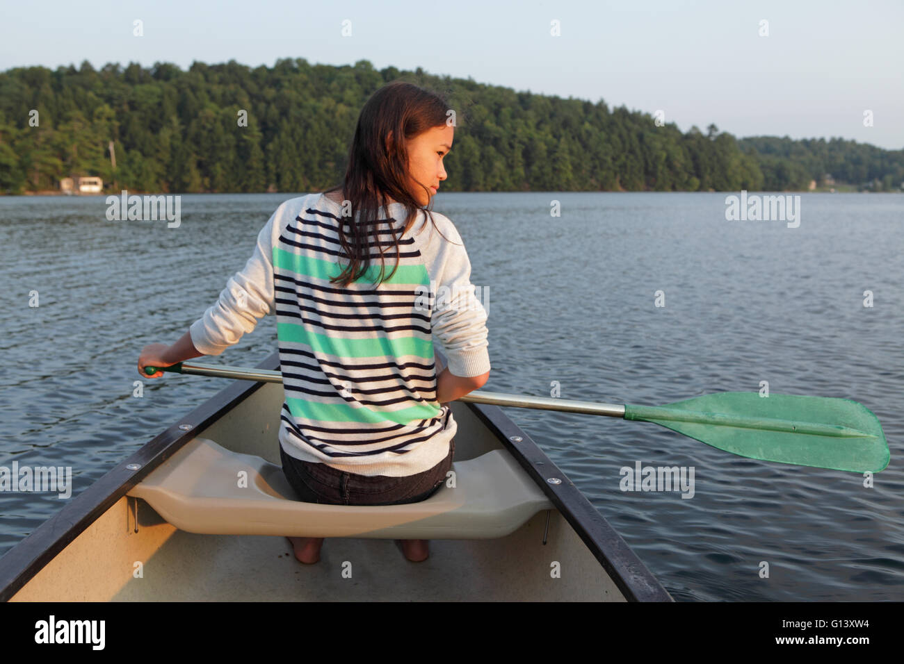 Young girl paddling a canoe on a calm lake in Western Vermont in the summer - Stock Image
