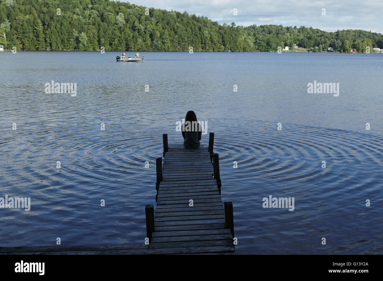 Girl making radiating ripples in a Vermont lake on a summer day - Stock Image