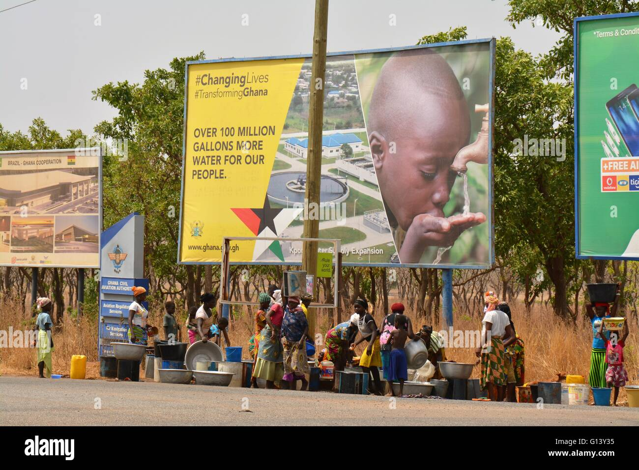 Fetching water under an 'More Water' for our people bill board, Ghana, Tamale - Stock Image