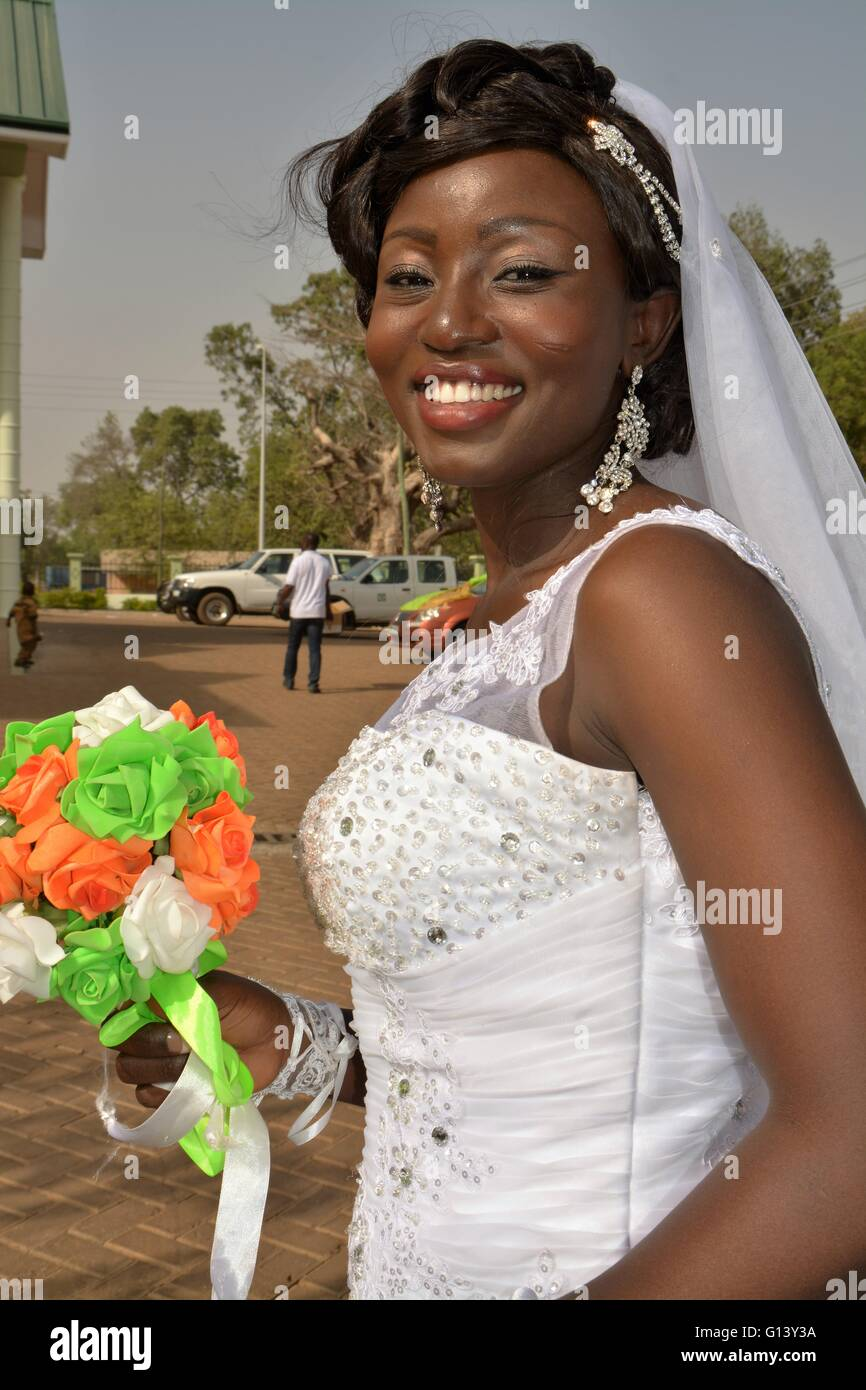 Traditional and Catholic wedding in Bolgatanga, Ghana. Braid holding an colorful flower arrangement - Stock Image