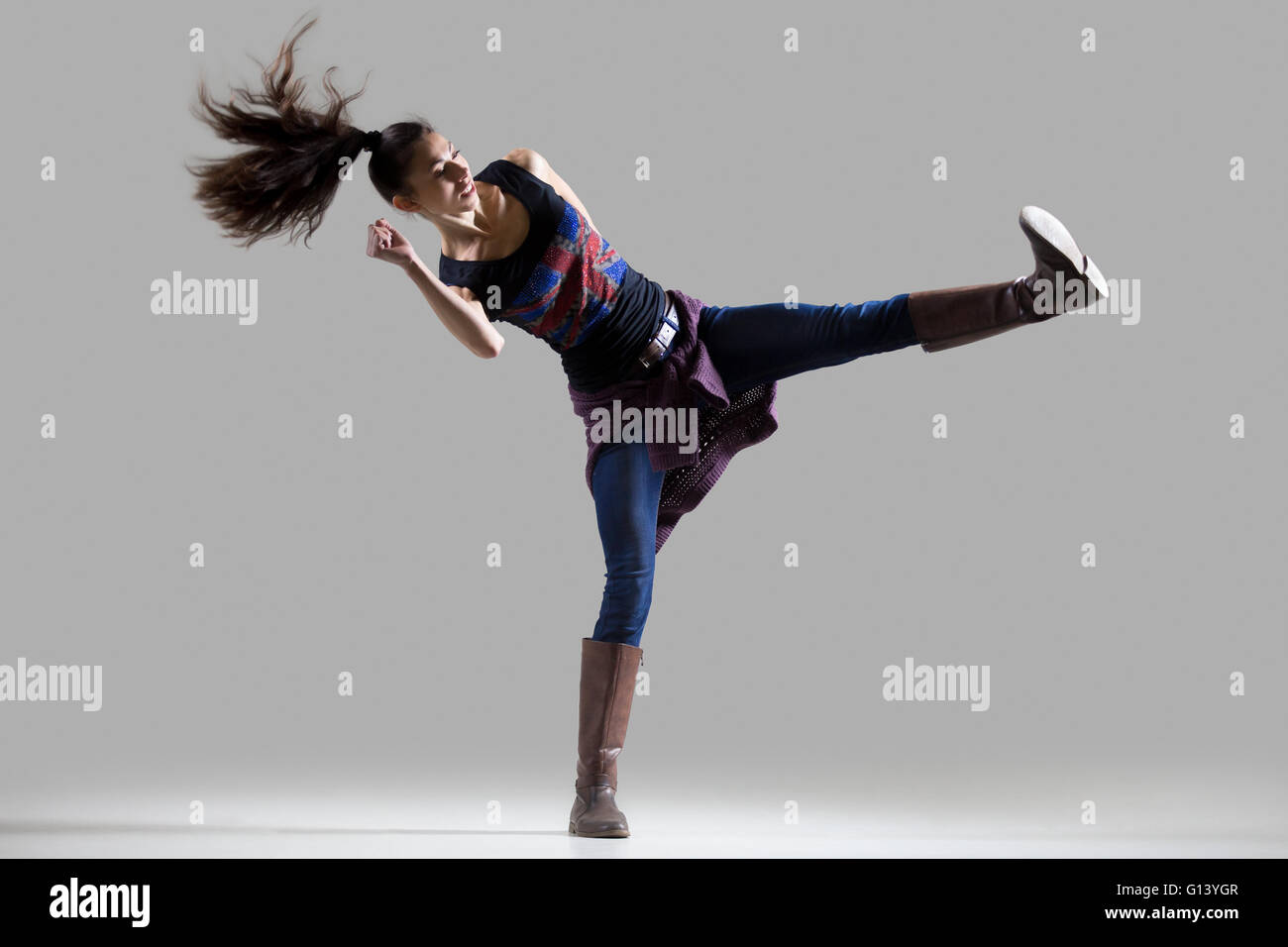 Stylish dancing young woman portrait. Fit athletic girl wearing British flag tank top warming up, working out - Stock Image