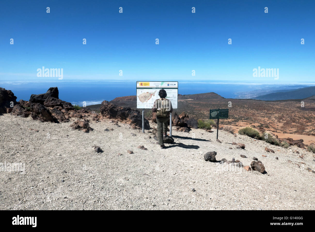 A young hiker checks the informative panel in Montaña Blanca, at the foot of El Teide, in the Cañadas. Tenerife, Stock Photo