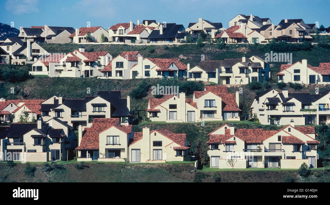 Suburban homes with red tile roofs and beige stucco facades line up in parallel on a multitiered hillside in the - Stock Image