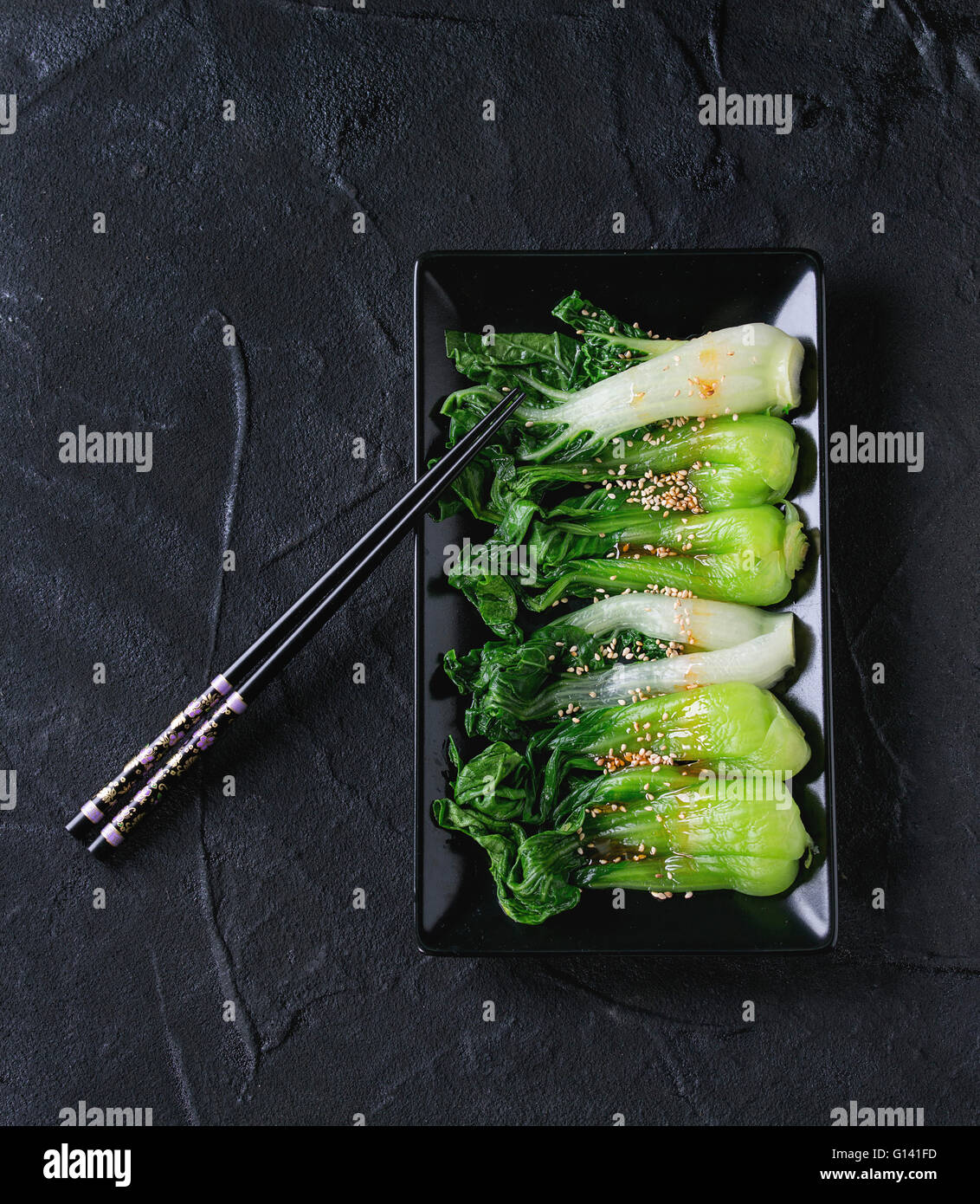 Cooked bok choy with sesame seeds and chili pepper olive oil in black square ceramic plate with black chopsticks - Stock Image