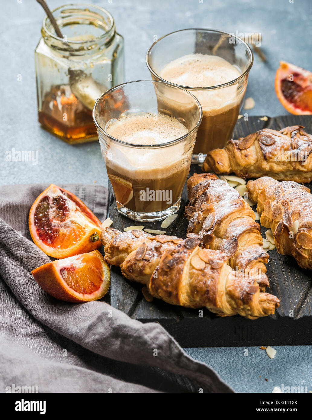 Italian style home breakfast. Latte coffee, almond croissants and red bloody oranges on dark wooden serving  board - Stock Image