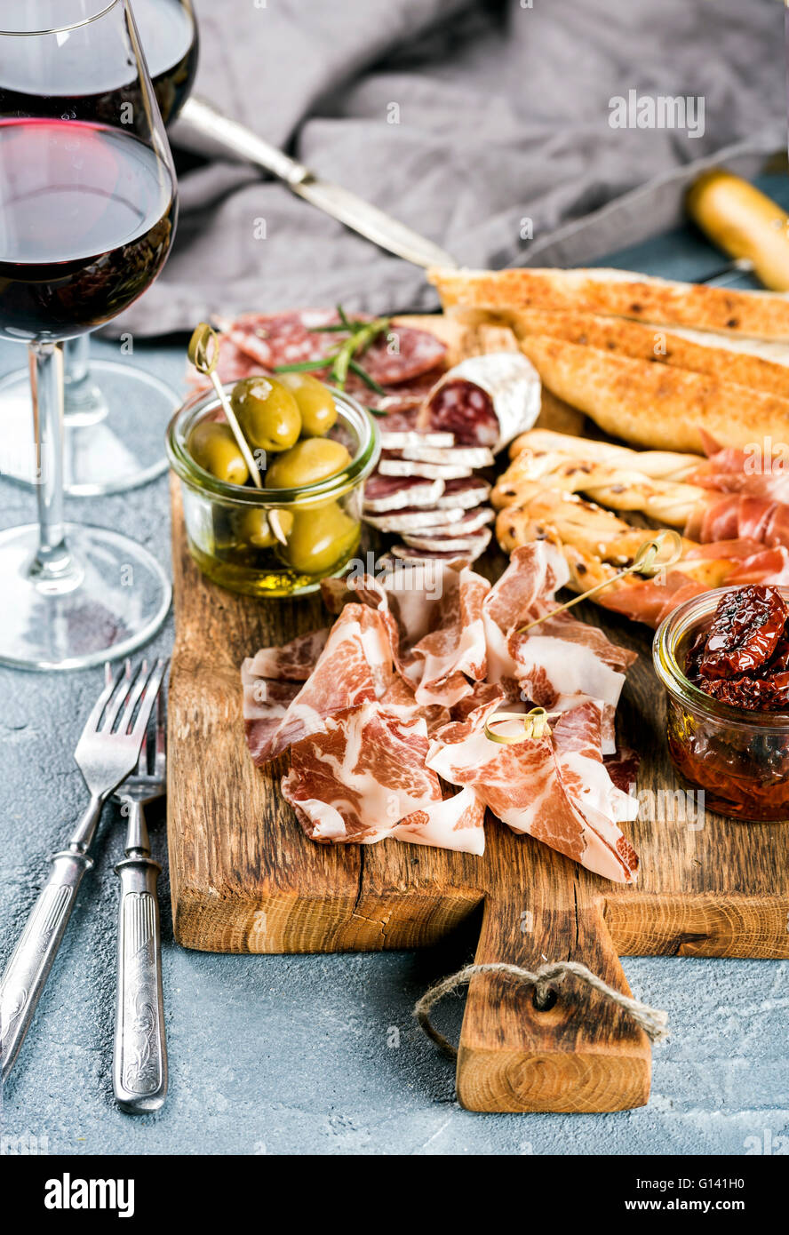 Meat appetizer selection. Salami, prosciutto, bread sticks, baguette, olives and sun-dried tomatoes, two glasses - Stock Image